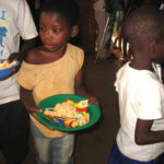 Maoni Orphanage kids in line for food